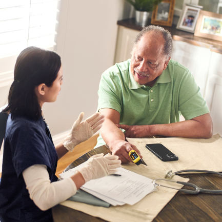 Patient getting vitals checked by health care worker at home