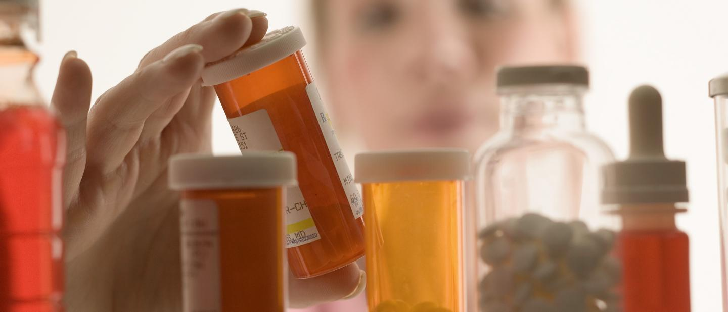 Woman gazing into a crowded medicine cabinet