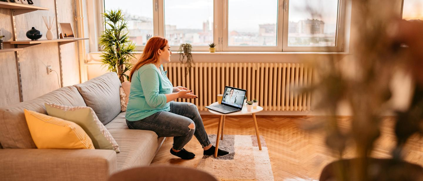 Woman speaking with clinician via laptop
