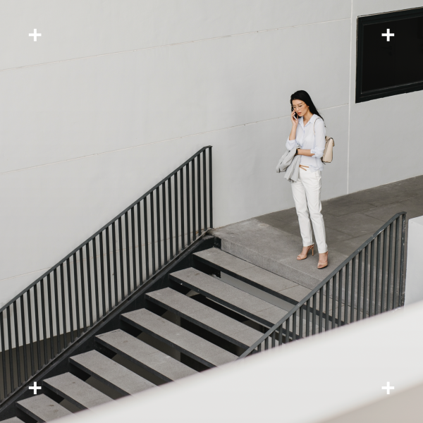 Woman on the phone atop a flight of stairs