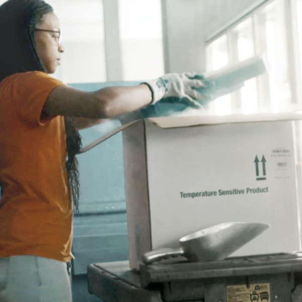 Health service representative packing pharmaceuticals in a shipping box for distribution