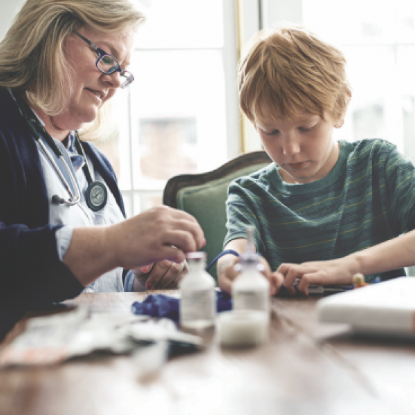 Healthcare Assistant administering medications to a young patient