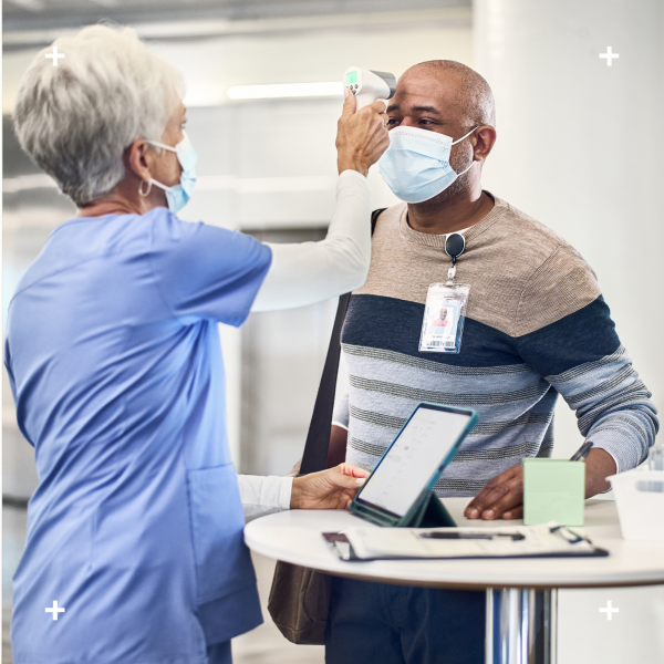 health care worker taking a patients temporal temperature